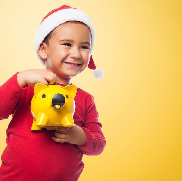 Kleine jongen met kerst muts met behulp van zijn nieuwe spaarpot