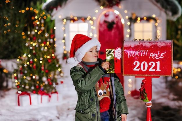 Kleine jongen met kerstmuts stuurt een brief naar de kerstman in een brievenbus