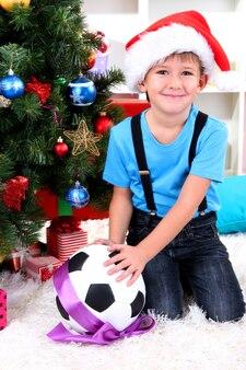 Kleine jongen met kerstmuts zit in de buurt van kerstboom met voetbalbal