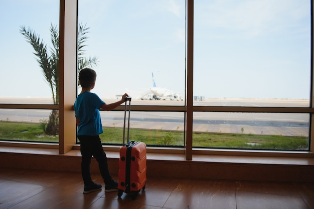 Kleine jongen met koffer te wachten op de luchthaven Premium Foto