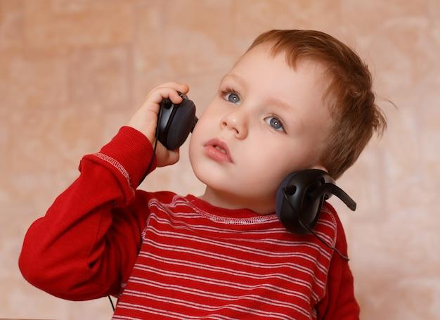 Kleine jongen met koptelefoon luisteren naar muziek en zingen