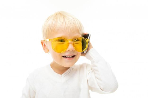 Kleine jongen met kort blond haar, blauwe ogen, schattig uiterlijk, een wit jasje, lichtblauwe broek, staand met een gele bril en pratend aan de telefoon