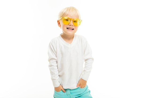 Kleine jongen met kort blond haar en gele zonnebril