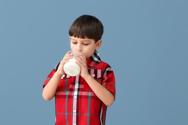 Kleine jongen met melk op kleur Premium Foto