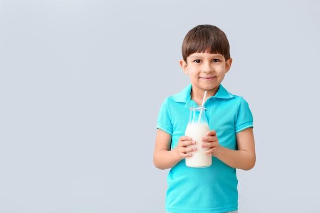 Kleine jongen met melk op licht Premium Foto