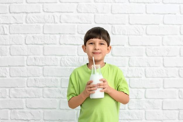 Kleine jongen met melk op witte baksteen