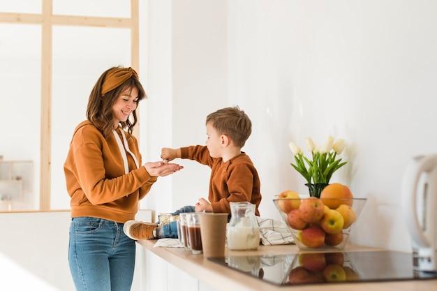 Kleine jongen met moeder in de keuken