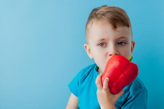 Kleine jongen met peper in zijn handen op blauw