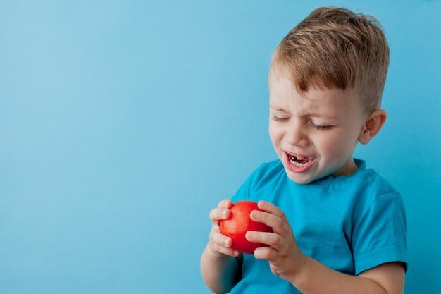 Kleine jongen met peper in zijn handen op blauwe achtergrond. veganistisch en gezond concept