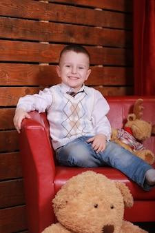 Kleine jongen met plezier op de bank in de kerststudio in het rood. kerstboom en teddybeer op de muur.