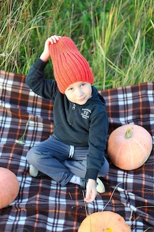 Kleine jongen met plezier tijdens een rondleiding door een pompoenboerderij in de herfst