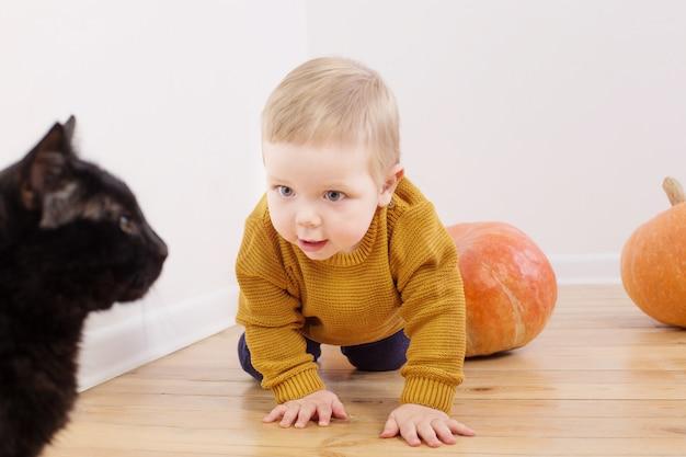 Kleine jongen met pompoenen op houten vloer