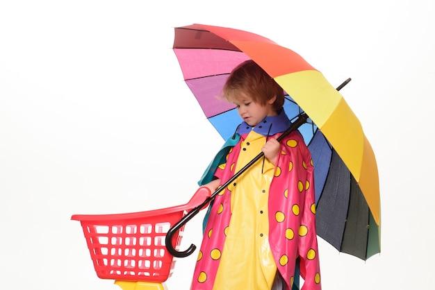 Kleine jongen met regenboogkleurige paraplu geïsoleerd op een witte muur.