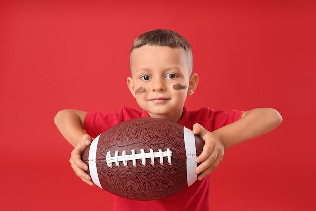 Kleine jongen met rugbybal op kleurruimte