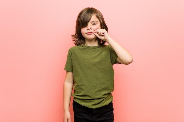 Kleine jongen met vingers op lippen die een geheim bewaren.
