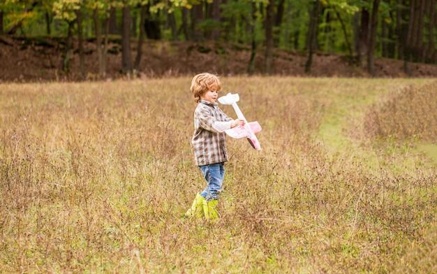 Kleine jongen met vliegtuig. een klein kind droomt ervan piloot te worden. kind spelen met speelgoed vliegtuig. gelukkig kind spelen. gelukkig kind buiten spelen. gelukkig jongen speel vliegtuig.