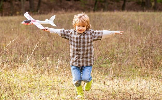 Kleine jongen met vliegtuig. kleine jongen droomt ervan piloot te worden.