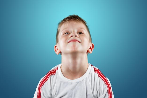 Kleine jongen met zijn handen omhoog glimlachen op een blauw