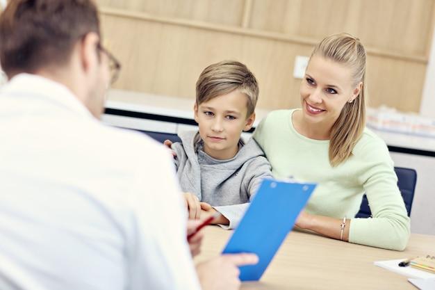 Kleine jongen met zijn moeder in kliniek onderzocht door kinderarts pediatric