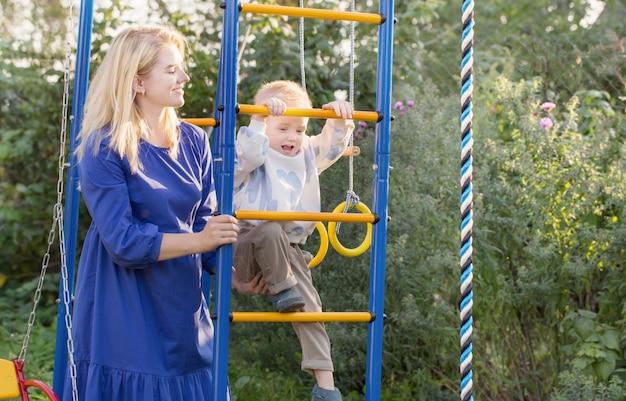 Kleine jongen met zijn moeder op speelplaats op zomerdag