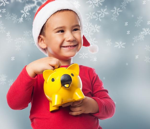 Kleine jongen met zijn spaarpot met sneeuwvlokken achtergrond