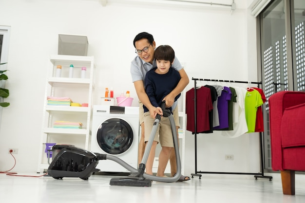 Kleine jongen met zijn vader gebruikt de kamer stofzuigen. vader en zoon doen de schoonmaak in het huis.