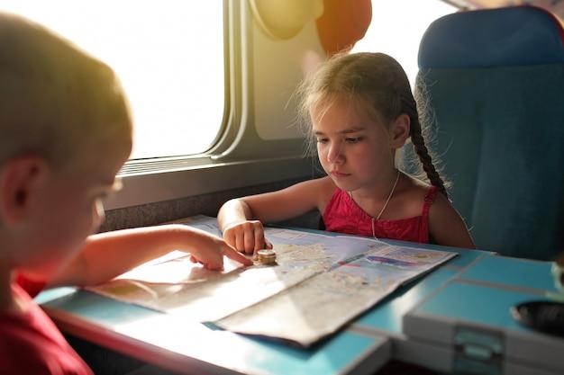 Kleine jongen met zijn zus bespreken hun economie vakantie tijdens het reizen met de trein