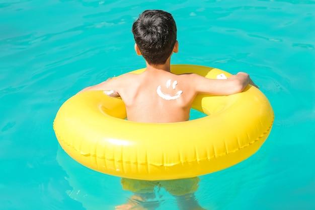 Kleine jongen met zonnebrandcrème op zijn lichaam en opblaasbare ring in zwembad