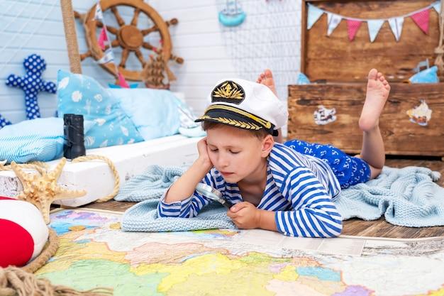 Kleine jongen naar het beeld van een zeeman die in zijn kamer speelt.
