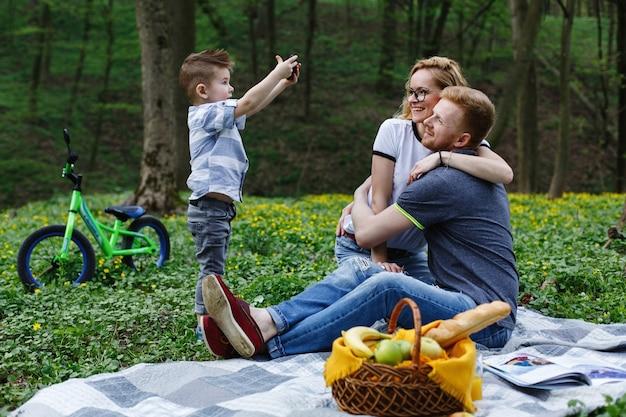 Kleine jongen neemt een foto van zijn ouders op de smartphone tijdens een picknick in het park