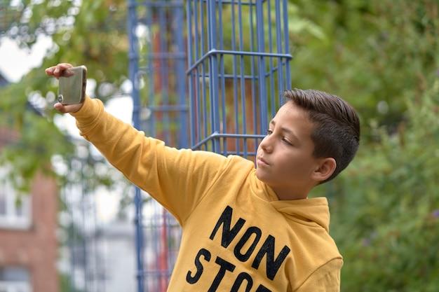 Kleine jongen neemt een selfie op straat met zijn telefoon