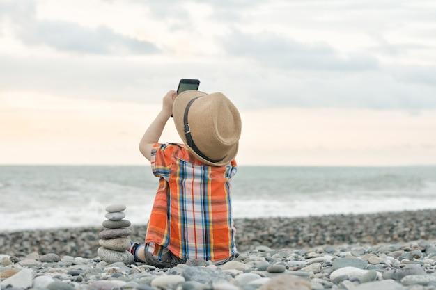 Kleine jongen neemt foto's op de slimme telefoon. zit op een kiezelstrand