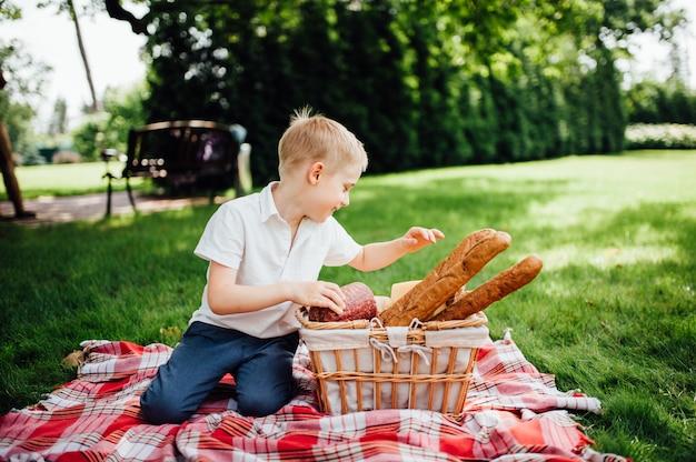 Kleine jongen neemt zijn handen het eten in de tuin