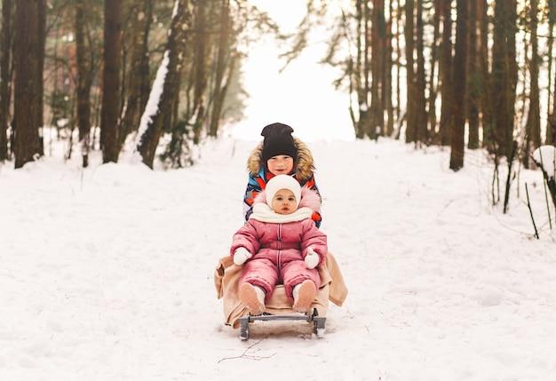 Kleine jongen neemt zijn zusje in de winter mee op een slee.