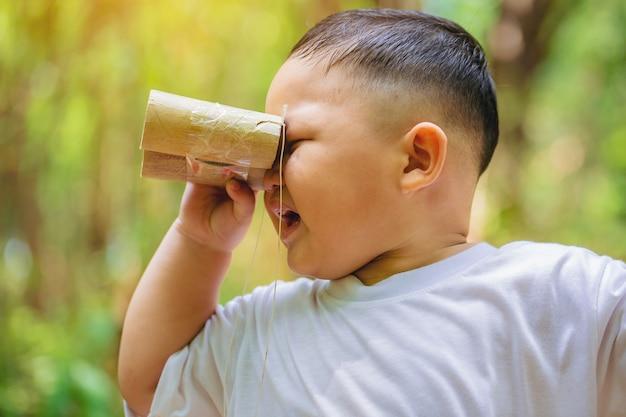 Kleine jongen ontdekkingsreiziger en avontuur met speelgoed verrekijker op achtertuin bos