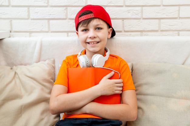 Kleine jongen op bank met boek