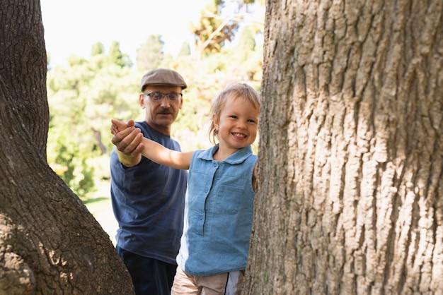 Kleine jongen op bomen met opa