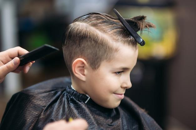 Kleine jongen op een kapsel in de kapper zit op een stoel