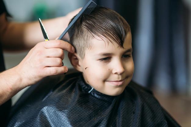 Kleine jongen op een kapsel in de kapper zit op een stoel.