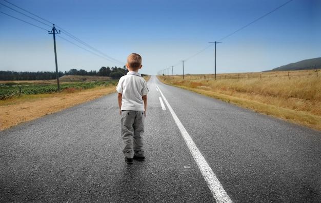 Kleine jongen op een lege weg