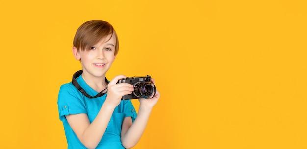 Kleine jongen op het nemen van een foto met behulp van een vintage camera. kind in studio met professionele camera. jongen met behulp van een camera
