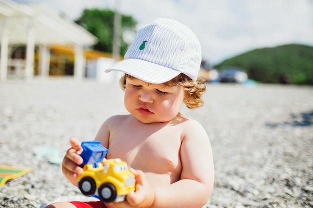 Kleine jongen op het strand met zonnebrandcrème op zijn neus