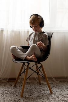 Kleine jongen op stoel thuis met behulp van tablet en koptelefoon
