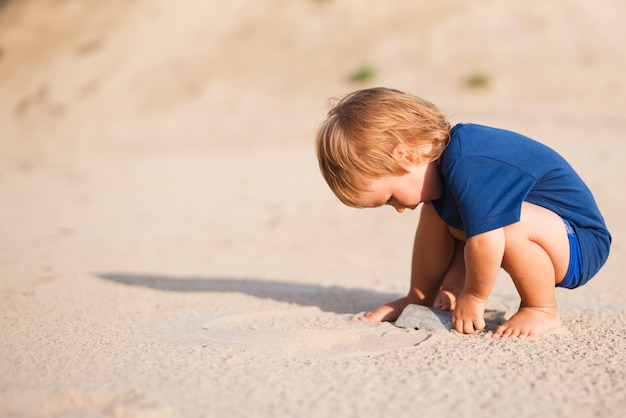 Kleine jongen op strand spelen met zand