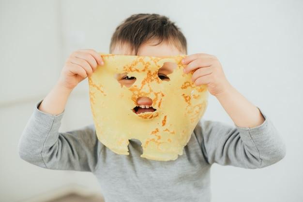 Kleine jongen pannenkoeken eten en spelen met een pannenkoek, plezier en cool