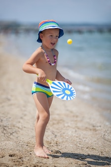 Kleine jongen peddels spelen op het strand