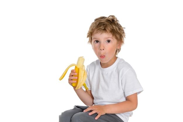 Kleine jongen pelt een banaan en neemt een grote hap, houdt hem in zijn mond en probeert te kauwen.