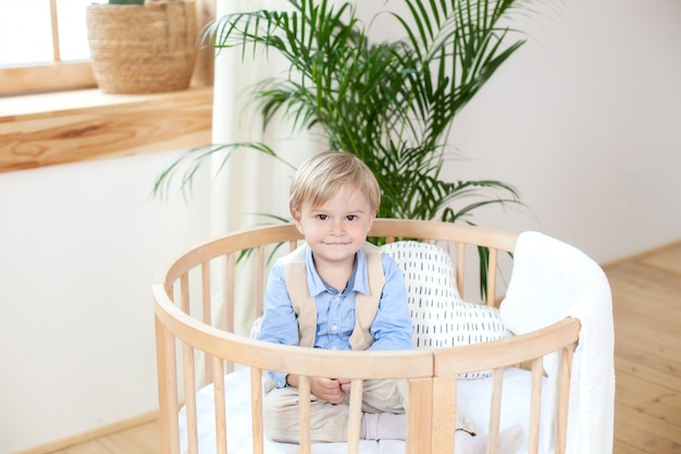 Kleine jongen. portret van een gelukkige jongen die in een babywieg speelt. de jongen zit alleen in een wieg in de kinderkamer. eenzame baby blijft in de wieg. waif kind. het kind in bed lacht. interieur kinderkamer.