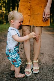 Kleine jongen poseren met mama's benen huilen