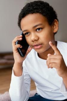 Kleine jongen praten op mobiel